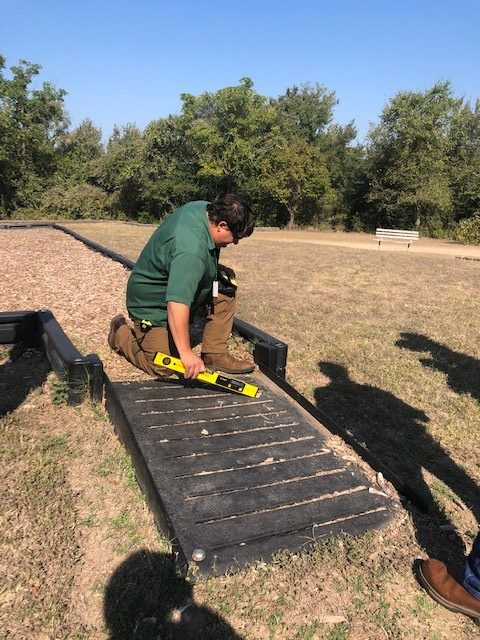 A trainee measures the slope of the ramp into a playground area at McKinney Falls State Park as part of the Access to Parks and Recreation workshop.