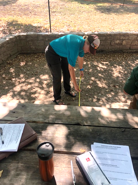 "A Texas Parks and Wildlife Department staff member measures the clearance around a picnic table as part of the ""classroom in the field"" portion of the training."